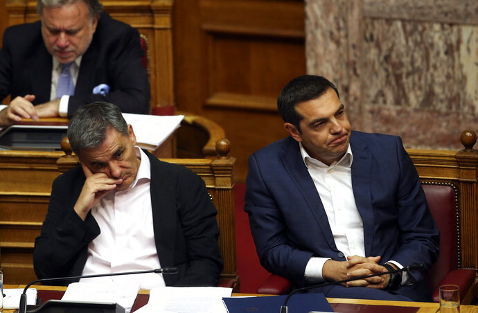 Greek Prime Minister Alexis Tsipras, right, and Finance Minister Euclid Tsakalotos attend a parliamentary session in Athens, on Thursday, June 14, 2018. The head of Greece's main opposition party Kyriakos Mitsotakis submitted a motion for a no-confidence vote in the government, objecting to a deal reached between the prime ministers of Greece and Macedonia to settle a decades-old dispute over Macedonia's name. (AP Photo/Petros Giannakouris)