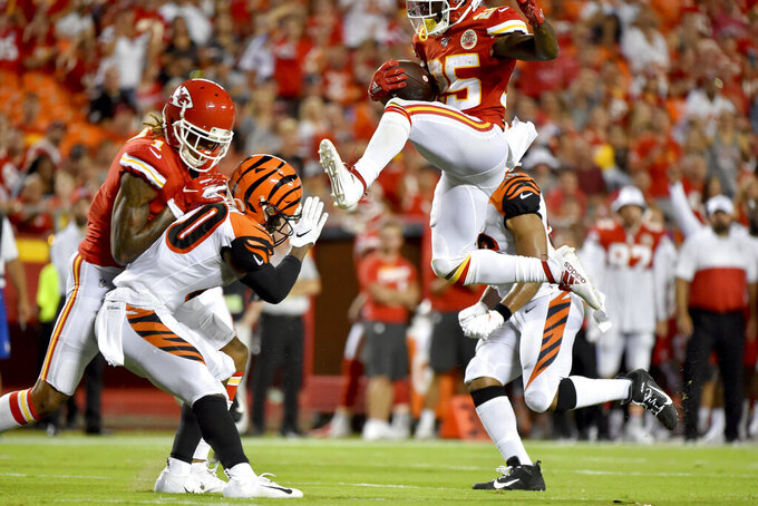 Kansas City Chiefs running back Darwin Thompson (25) tries to vault over Cincinnati Bengals safety Brandon Wilson (40), during the second half of an NFL preseason football game in Kansas City, Mo., Saturday, Aug. 10, 2019. (AP Photo/Ed Zurga)