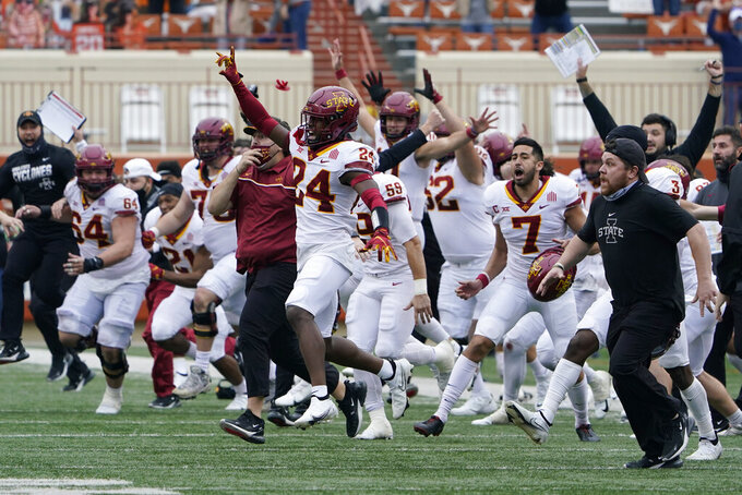 Iowa State players and coaches storm the field as they celebrate their win over Texas in an NCAA college football game, Friday, Nov. 27, 2020, in Austin, Texas. (AP Photo/Eric Gay)