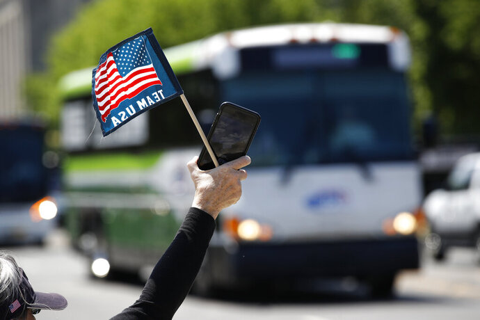 "FILE - In this May 13, 2020, file photo, tour guide Barbara Western waves a flag in support of bus and motor coach operators as they circle the National Mall in Washington. As a candidate for the White House, President Donald Trump once said he wanted ""whatever is best"" for the residents of the nation's capital. But over the course of his more than three years in office a disconnect between the president and District of Columbia has emerged -- a chasm that has only grown during the coronavirus pandemic. (AP Photo/Patrick Semansky, File)"