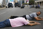 Anti-government protesters lie on the ground as they block a main highway, in Beirut, Lebanon, Saturday, Oct. 26, 2019. Lebanese security forces pushed and dragged away protesters who refused to move from roadblocks in central Beirut on Saturday, to reopen roads closed during a campaign of civil disobedience. (AP Photo/Hussein Malla)