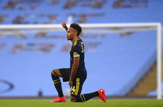 Arsenal's Pierre-Emerick Aubameyang takes a knee in support of the Black Lives Matter movement before the English Premier League soccer match between Manchester City and Arsenal at the Etihad Stadium in Manchester, England, Wednesday, June 17, 2020. The English Premier League resumes Wednesday after its three-month suspension because of the coronavirus outbreak. (Laurence Griffiths/Pool via AP)
