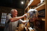 Former Dallas Cowboys and NFL football great Cliff Harris pulls out the helmet he wore during his playing days during an interview at his home in North Dallas, Wednesday, June 30, 2021. Harris and receiver Drew Pearson, who also will be inducted this year as part of the class of 2021, are the first undrafted Cowboys among their 15 players in the Hall of Fame. (AP Photo/LM Otero)