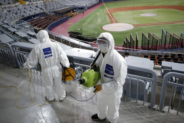 Workers wearing protective gears disinfect as a precaution against the new coronavirus at Gocheok Sky Dome in Seoul, South Korea, Tuesday, March 17, 2020. The Korea Baseball Organization has postponed the start of new season to prevent the spread of the new coronavirus. For most people, the new coronavirus causes only mild or moderate symptoms. For some it can cause more severe illness. (AP Photo/Lee Jin-man)