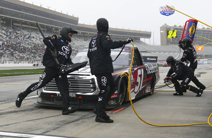 Kyle Busch is tend to by crew members during a pit stop in a NASCAR Truck Series auto race at Atlanta Motor Speedway, Saturday, Feb. 23, 2019, in Hampton, Ga. (AP Photo/John Amis)
