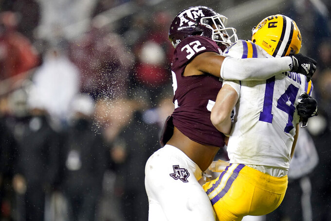 Texas A&M linebacker Andre White Jr. (32) sacks LSU quarterback Max Johnson (14) for a loss during the third quarter of an NCAA college football game Saturday, Nov. 28, 2020, in College Station, Texas. (AP Photo/Sam Craft)