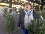 In this Saturday, Dec. 7, 2019 photo, Sandy Parsons speaks while tending to Christmas trees for sale on her lot at the Capitol Market in Charleston, W.Va. Parsons never received her order of 350 trees this year from a North Carolina farm, citing a short supply. Instead, she was sent a few much-smaller trees. Christmas trees are in tight supply again this year across the United States, depending upon location and seller, as the industry continues bouncing back from the Great Recession. (AP Photo/John Raby)