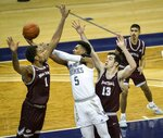 Washington's Jamal Bey (5) looks for a shot in the lane while defended by Montana's Michael Steadman (1) and Josh Bannan (13) during the first half of an NCAA college basketball game, Wednesday, Dec. 16, 2020, at Alaska Airlines Arena in Seattle. (Dean Rutz/The Seattle Times via AP)