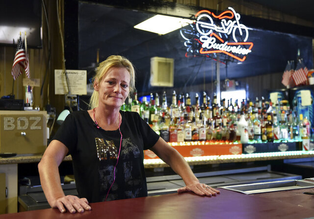 Owner of Big Daddy Zane's Gabrielle Ellison poses for a photo behind the bar top of her establishment in Odessa, Texas, Friday, June 26, 2020. Ellison was operating her bar in violation of Texas Gov. Greg Abbott's new order that shut bars back down and limits restaurants' capacities to 50% following a surge in coronavirus cases. (Eli Hartman/Odessa American via AP)