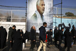 Mourners walk back from a funeral ceremony for Iranian Gen. Qassem Soleimani in front of the former U.S. Embassy, who was killed with others in Iraq by a Friday U.S. drone attack, Monday, Jan. 6, 2020. Funeral ceremonies for Soleimani drew a crowd said by police to be in the millions, on Monday in Tehran, where his replacement vowed to take revenge. (AP Photo/Vahid Salemi)