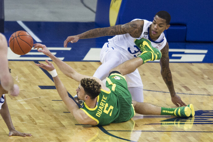 Oregon's Chris Duarte throws a pass after scrambling for the ball with Seton Hall's Shavar Reynolds Jr. during the second half of an NCAA college basketball game in Omaha, Neb., Friday, Dec. 4, 2020. (AP Photo/Kayla Wolf)