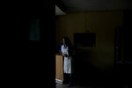 Estela Garcia stands inside the grocery shop where she works in Caracas, Venezuela, Tuesday, March 26, 2019. Much of Venezuela remains without electricity as a new power outage spread across the country. (AP Photo/Natacha Pisarenko)