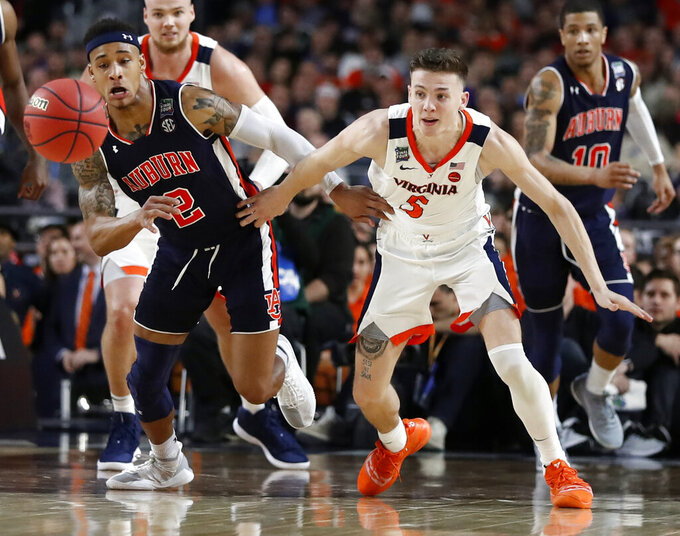 Auburn's Bryce Brown (2) and Virginia's Kyle Guy (5) battle for a loose ball during the second half in the semifinals of the Final Four NCAA college basketball tournament, Saturday, April 6, 2019, in Minneapolis. (AP Photo/Jeff Roberson)