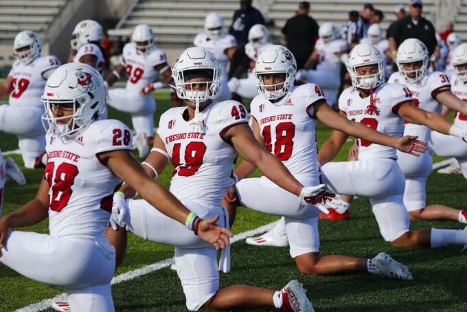 Fresno State players warm up before the start of an NCAA college football game against Hawaii, Saturday, Oct. 2, 2021, in Honolulu. (AP Photo/Marco Garcia)