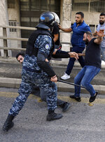 A Lebanese riot policeman clashes with Hezbollah supporters during a protest in Beirut, Lebanon, Tuesday, Oct. 29, 2019. Beirut residents have scuffled with Lebanese protesters blocking a main thoroughfare, prompting riot police to move to separate them. The tension Tuesday comes on the 13th day of anti-government protests. (AP Photo/Bilal Hussein)