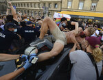 An activist climbs onto a police car to protest the detention of an LGBT activist in Warsaw, Poland, Friday, Aug. 7, 2020. The incident comes amid rising tensions in Poland between LGBT activists and a conservative government that is opposed to LGBT rights. (AP Photo/Czarek Sokolowski)