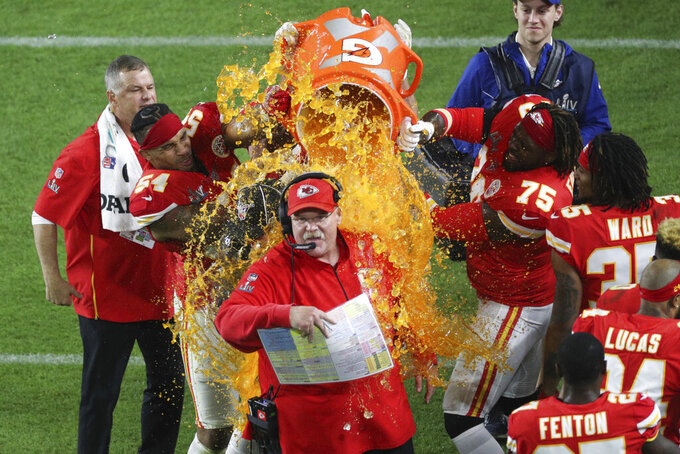 Kansas City Chiefs outside linebacker Damien Wilson (54), tight end Travis Kelce (87), and offensive tackle Cameron Erving (75) celebrate after dumping Gatorade on Kansas City Chiefs head coach Andy Reid during the NFL Super Bowl football game against the San Francisco 49ers, Sunday, Feb. 2, 2020 in Miami Gardens, Fla. The Chiefs defeated the 49ers 31-20.(Margaret Bowles via AP)