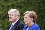 German Chancellor Angela Merkel welcomes Britain's Prime Minister Boris Johnson for a meeting at the Chancellery in Berlin, Germany, Wednesday, Aug. 21, 2019. (AP Photo/Michael Sohn)