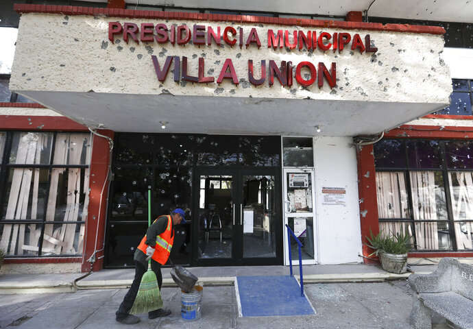 A worker cleans up outside City Hall, riddled with bullet holes, in Villa Union, Mexico, Monday, Dec. 2, 2019. The small town near the U.S.-Mexico border began cleaning up Monday even as fear persisted after 22 people were killed in a weekend gunbattle between a heavily armed drug cartel assault group and security forces. (AP Photo/Eduardo Verdugo)