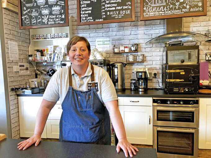 Caroline Atkinson, owner of the Rose Coffee House poses for a photo as she prepares to reopen, in Belmont, Durham, England, Thursday May 13, 2021. Travelers are packing their bags, café-owners are polishing their cutlery and stage performers are warming up as Britain prepared for a major step out of lockdown. But excitement at the reopening of travel and hospitality vied with anxiety about a more contagious variant spreading in the country (Tom Wilkinson/PA via AP)