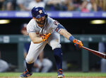 Houston Astros' Jose Altuve reaches out to connect for an RBI-double off Colorado Rockies relief pitcher Bryan Shaw in the seventh inning of a baseball game Tuesday, July 2, 2019, in Denver. (AP Photo/David Zalubowski)