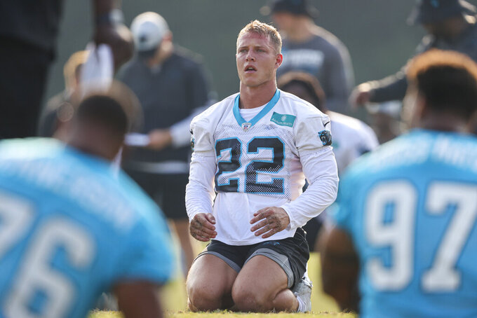 Carolina Panthers running back Christian McCaffreysits on the field during stretching at the NFL football team's training camp in Spartanburg, S.C., Tuesday, Aug. 10, 2021. (AP Photo/Nell Redmond)