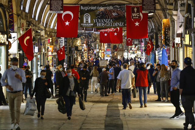 People wearing protective face masks against the spread of coronavirus, walk at the iconic 15th century Grand Bazaar in Istanbul as it reopens, Monday June 1, 2020, following weeks of closure due to the coronavirus pandemic. Turkish Airlines resumed limited domestic flights, restaurants welcomed sit-in customers and beaches and museums reopened as Turkey's broadest easing of coronavirus restrictions came into effect following a slowdown in confirmed COVID-19 infections and deaths in the country. (AP Photo/Emrah Gurel)