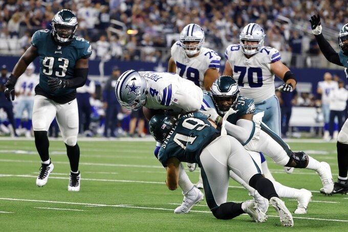 Dallas Cowboys quarterback Dak Prescott (4) is stopped as he runs the ball by Philadelphia Eagles linebacker Alex Singleton (49) and defensive end Josh Sweat (94) in the second half of an NFL football game in Arlington, Texas, Monday, Sept. 27, 2021. (AP Photo/Michael Ainsworth)