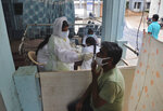 A health worker takes a nasal swab sample at a COVID-19 testing center in Hyderabad, India, Wednesday, Oct. 7, 2020. India is the world's second most coronavirus affected country after the United States. (AP Photo/Mahesh Kumar A.)