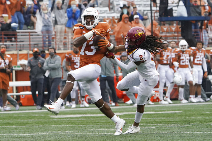 Texas wide receiver Brennan Eagles (13) pulls down a pass in front of Iowa State defensive back Datrone Young (2) during the first half of an NCAA college football game Friday, Nov. 27, 2020, in Austin, Texas. (AP Photo/Eric Gay)