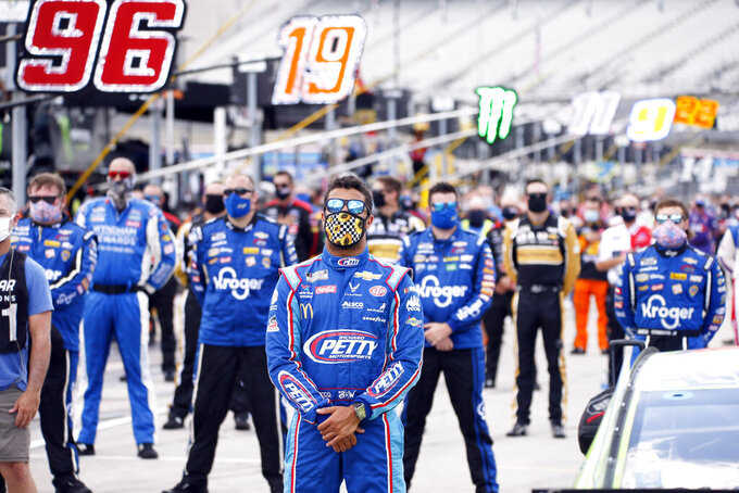 "FILE - Bubba Wallace, center, stands on pit road during the playing of ""America the Beautiful"" prior to a NASCAR Cup Series auto race at Texas Motor Speedway in Fort Worth, Texas, Sunday, July 19, 2020. NASCAR drivers don't plan to boycott Saturday night's, Aug. 29 race at Daytona International Speedway to raise awareness of social and racial injustices. Bubba Wallace, the only fulltime Black driver in the elite Cup Series, said that decision should not be interpreted as ""turning away from the dark and evil acts that have taken over our nation."" (AP Photo/Ray Carlin, File)"