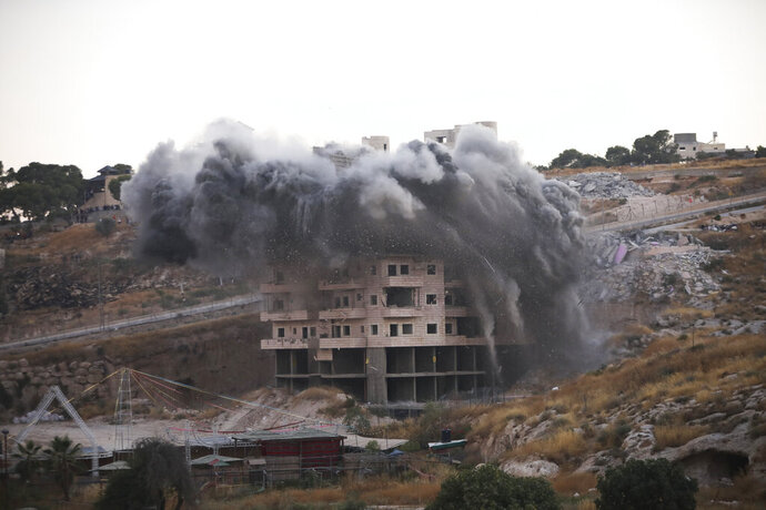 File - In this Monday, July 22, 2019 file photo, Israeli forces blow up a building in a Palestinian village of Sur Baher, east Jerusalem. Israeli advocacy group has found that Israeli authorities demolished homes in Palestinian areas of east Jerusalem at a significantly higher rate in 2019 than the previous year. (AP Photo/Mahmoud Illean, File)