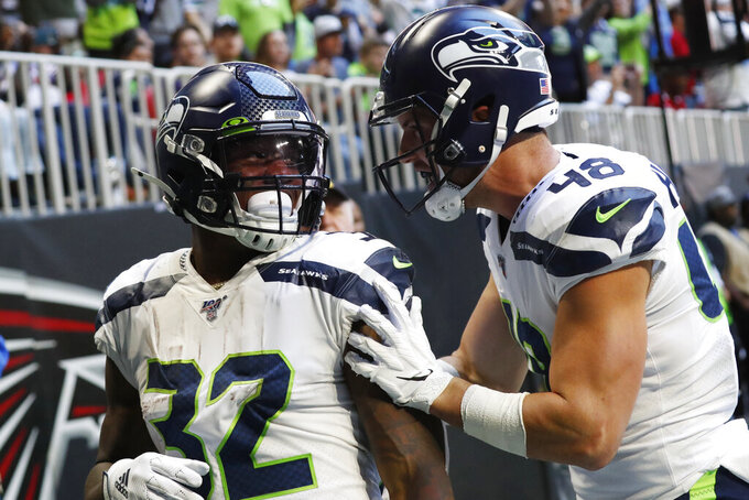 Seattle Seahawks running back Chris Carson (32) celebrates is touchdown with Seattle Seahawks tight end Jacob Hollister (48) against the Atlanta Falcons during the first half of an NFL football game, Sunday, Oct. 27, 2019, in Atlanta. (AP Photo/John Bazemore)