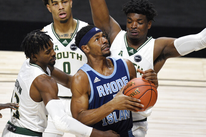 Rhode Island's Antwan Walker goes to the basket as South Florida's Justin Brown, left, David Collins, back center, and Alexis Yetna defend during the first half of an NCAA college basketball game Saturday, Nov. 28, 2020, in Uncasville, Conn. (AP Photo/Jessica Hill)