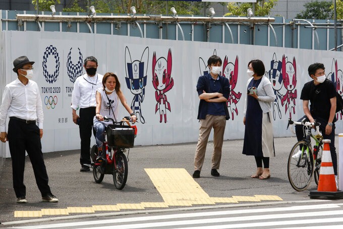 People stand by posters to promote the Tokyo Olympic Games scheduled to start in the summer of 2021, in Tokyo, Monday, May 24, 2021. (AP Photo/Koji Sasahara)