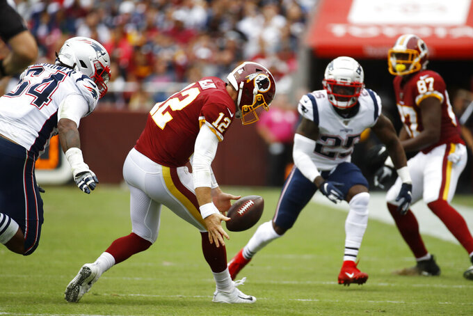 Washington Redskins quarterback Colt McCoy (12) recoveres his own fumble against the New England Patriots during the first half of an NFL football game, Sunday, Oct. 6, 2019, in Washington. (AP Photo/Patrick Semansky)