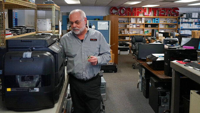 """Independent repair shop owner Curtis Jones works on an Epson printer at The Technology Center in Sparks, Nev., Tuesday, March 30, 2021. Jones is among a group of independent repair shop owners who say tech companies have made it increasingly difficult to access parts and schematics needed to fix devices. He wants the state Legislature to pass a """"Right to Repair"""" bill that would require manufacturers provide independent repair shops the information needed to fix devices. (AP Photo/Samuel Metz)"""
