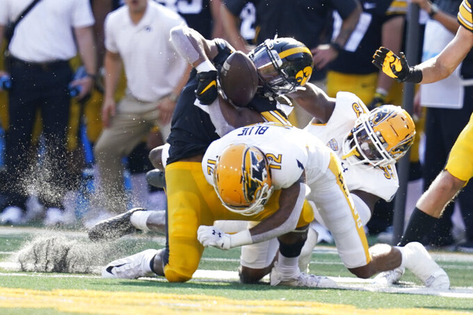 Iowa running back Ivory Kelly-Martin (21) fumbles the ball as he is hit by Kent State cornerback Capone Blue (12) and linebacker Marvin Pierre (33) during the first half of an NCAA college football game, Saturday, Sept. 18, 2021, in Iowa City, Iowa. (AP Photo/Charlie Neibergall)