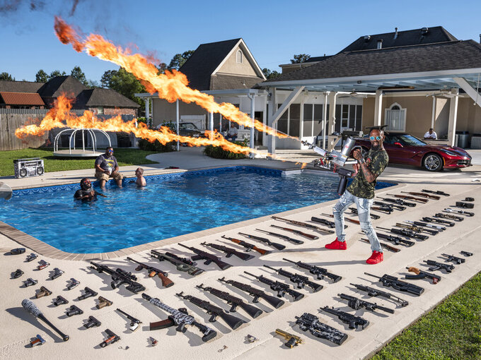 In this image released by World Press Photo, Thursday April 15, 2021, by Gabriele Galimberti for National Geographic, part of a series titled The 'Ameriguns' which won first prize in the Portraits Stories category, shows Torrell Jasper (35) poses with his firearms in the backyard of his house in Schriever, Louisiana, USA, on April 14, 2019. A former US Marine, he learned to shoot from his father as a child. (Gabriele Galimberti for National Geographic, World Press Photo via AP)