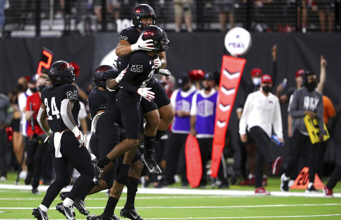 UNLV defensive back Cameron Oliver (25) celebrates with teammates after an interception of an Eastern Washington pass during the first half of an NCAA college football game Thursday, Sept. 2, 2021, in Las Vegas. (Steve Marcus/Las Vegas Sun via AP)