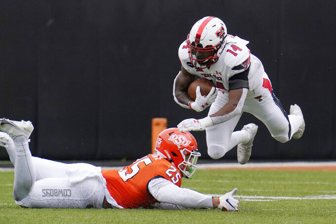 Texas Tech running back Xavier White (14) is upended by Oklahoma State safety Jason Taylor II (25) in the second half of an NCAA college football game in Stillwater, Okla., Saturday, Nov. 28, 2020. (AP Photo/Sue Ogrocki)