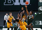 Michigan State's Aaron Henry, right, blocks a shot by Oakland's Rashad Williams (1) as Oakland's Blake Lampman, left, and Michigan State's Rocket Watts (2) and Malik Hall, rear, watch during the first half of an NCAA college basketball game, Sunday, Dec. 13, 2020, in East Lansing, Mich. (AP Photo/Al Goldis)