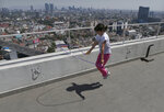 "Staying home after her school canceled classes due to the spread of the new coronavirus, Sofia Cortes jumps rope on the roof of a building in Mexico City,Tuesday, March 31, 2020. Mexico's government has broadened its shutdown of ""non essential activities,"" and prohibited gatherings of more than 50 people as a way to help slow down the spread of COVID-19. The one-month emergency measures will be in effect from March 30 to April 30. (AP Photo/Marco UGarte)"
