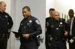San Francisco Police Chief William Scott, foreground, walks to the podium at a news conference, Tuesday, May 21, 2019, in San Francisco. Police agreed to return property seized from a San Francisco journalist in a raid, but the decision did little to ease tensions in the case, which has alarmed journalism advocates and put pressure on city leaders. Authorities have said the May 10 raids on freelancer Bryan Carmody's home and office were part of an investigation into what police called the illegal leak of a report on the death of former Public Defender Jeff Adachi, who died unexpectedly in February. (AP Photo/Eric Risberg)
