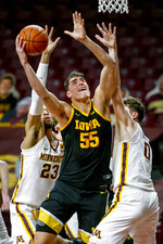 FILE - Iowa center Luka Garza (55) shoots between Minnesota forward Brandon Johnson (23) and center Liam Robbins (0) during the second half of an NCAA college basketball game in Minneapolis, in this Friday, Dec. 25, 2020, file photo. Garza was named The Associated Press men's basketball player of the year on Thursday, April 1, 2021.  (AP Photo/Bruce Kluckhohn, File)
