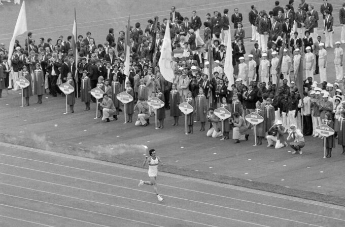 Soviet athlete Sergei Belov runs with the Olympic flame past the Olympic team from Afghanistan during opening ceremonies of the 1980 Summer Olympic Games in Moscow on Saturday, July 20, 1980. A number of teams boycotted the ceremony to protest Soviet intervention into Afghanistan. (AP Photo)
