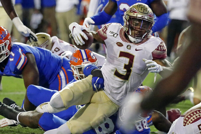 Florida State running back Cam Akers (3) runs for a first down against Florida on fourth=and-1 during the first half of an NCAA college football game, Saturday, Nov. 30, 2019, in Gainesville, Fla. (AP Photo/John Raoux)