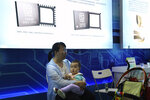 A woman carries a child near images of Chinese microchips during the National Science and Technology Week exhibition held at the Military Museum in Beijing on Friday, May 24, 2019. Stepping up Beijing's propaganda offensive in the tariffs standoff with Washington, Chinese state media on Friday accused the U.S. of seeking to