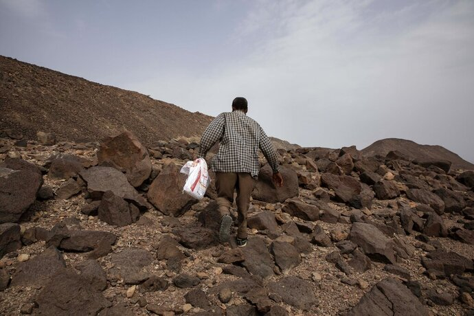 In this July 14, 2019 photo, 35-year-old Mohammed Eissa, an Ethiopian farmer, walks on the side of a highway, near Lac Assal, Djibouti. People here say they belong to migrants who like Eissa embarked on an epic journey of hundreds of miles, from villages and towns in Ethiopia and Somalia, through the Horn of Africa country of Djibouti, then across the sea and through the war-torn country of Yemen. (AP Photo/Nariman El-Mofty)