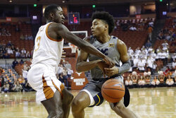 Texas guard Courtney Ramey (3) knocks the ball away from West Virginia guard Miles McBride (4) during the first half of an NCAA college basketball game, Monday, Feb. 24, 2020, in Austin, Texas. (AP Photo/Eric Gay)